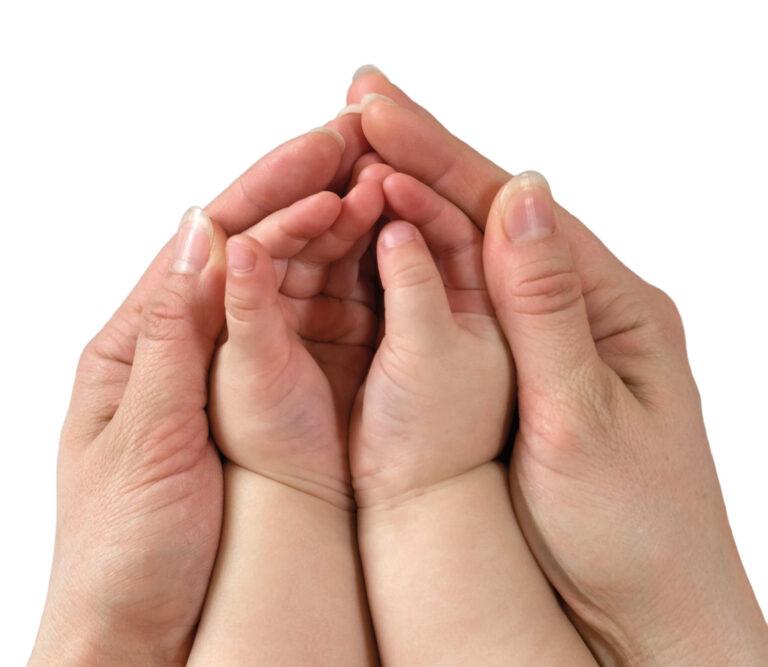 Prävention kann jede angehende Mutter betreiben. Hat die Mutter aber bei einer früheren Schwangerschaft unter einer peripartalen psychischen Krise gelitten, sollte sie bei einer erneuten Schwangerschaft unbedingt die Vorsorgemaßnahmen beachten. – Zwei Hände einer Erwachsenen umfassen die zwei Hände eines Babys.